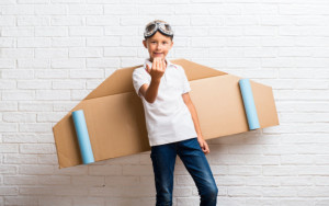 boy-playing-with-cardboard-airplane-wings-his-back-presenting-inviting-come_1368-26184